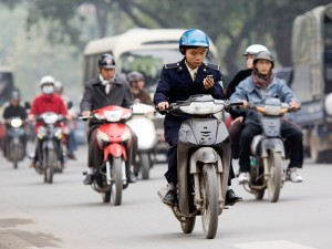A rider uses his cell phone while riding a scooter.